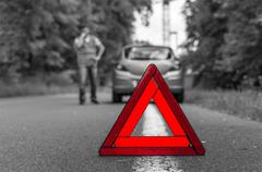 Broken car on the road and red warning triangle - black and white concept - stock photo