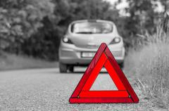 Red warning triangle and green broken car on the road - black and white conce - stock photo