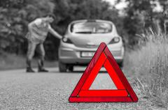 Broken car on the road and unhappy driver with red warning triangle - black a - stock photo