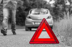 Broken car on the road and unhappy driver with red warning triangle - black a Stock Photos