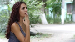 Beautiful brown hair busty girl portrait smoking cigarette in public place slow Stock Footage