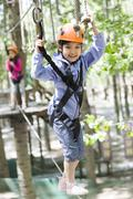 Happy children playing in tree top adventure park Stock Photos