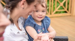 Little girl sitting on her mom's lap Stock Footage