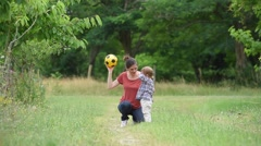 Mom and girl playing with ball in country path Stock Footage