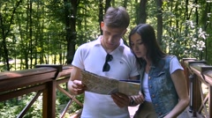 Young couple looking at the map and decide to go - stock footage