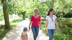3-generation family walking in park Stock Footage
