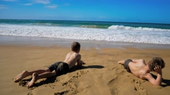 Two boys on the beach getting wet by the wave Stock Footage