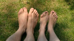 Man's and girl's feet dancing on the grass Stock Footage
