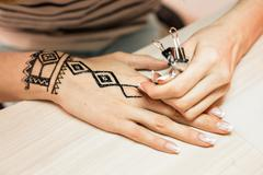 Artist applying henna tattoo on women hands. Mehndi is traditional Indian - stock photo