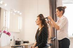 Woman at hairdresser with iron hair curler Stock Photos