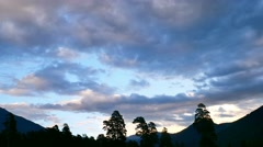 Timelapse of sunset with clouds in mountain forest, motionless silhouettes of Stock Footage