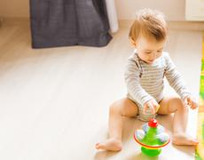 baby boy playing with toy indoors at home - stock photo