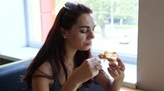 Young pretty girl portrait eat a piece of pizza in fast food restaurant pizzeria Stock Footage