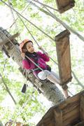 Little girl playing in tree top adventure park Kuvituskuvat