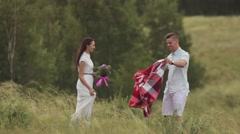 Couple in love spreads a blanket in a field Stock Footage