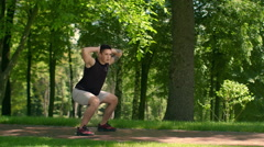 Outdoor fitness. Fitness man workout at park. Man doing squats. Fit man crouch Stock Footage