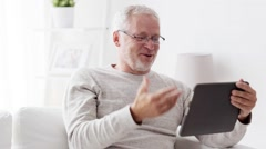 Senior man having video call on tablet pc at home 89 Stock Footage