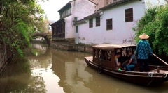 Traditional Chinese boat floats up a canal toward the bridge. Stock Footage