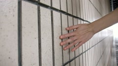 Female hand touching and sliding along the white tile wall. Stock Footage