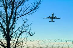 Plane taking off over the barbed wire and tree Stock Photos