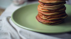American pancakes. Panning on pancakes stack on green plate at kitchen table - stock footage