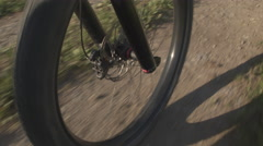 Electric offroad bicycle tire wheel spinning fast on gravel path Stock Footage