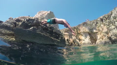 SLOW MOTION UNDERWATER: Man head jumping into refreshing water off a ocean cliff - stock footage