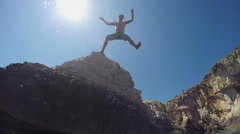 SLOW MOTION CLOSE UP UNDERWATER: Man jumping off a high ocean cliff into water Stock Footage
