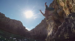 SLOW MOTION UNDERWATER: Happy man flip jumping into water on fun summer vacation - stock footage