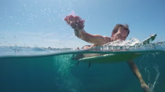 SLOW MOTION UNDERWATER: Smiling surfer man paddling on a surf in vast blue sea Stock Footage