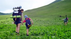 Mother and her son with Hiking backpacks walking in green summer mountains Stock Footage