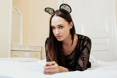 Young pretty brunette woman wearing sexy lace mouse ears, laying waiting Stock Photos