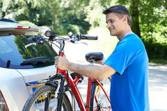 Mature Male Cyclist Taking Mountain Bike From Rack On Car Stock Photos