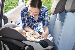 Mother Putting Baby Into Car Seat For Journey - stock photo