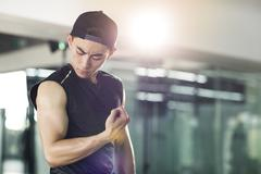 Young man in sports clothing flexing his muscles Stock Photos