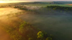 Foggy rural sunrise over farm fields and treetops Stock Footage