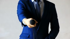 Man in business suit holding and giving out a microphone Stock Footage
