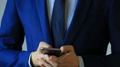 Closeup of Business man using a cellphone with two hands Stock Footage