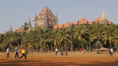 Bombay High Court with people playing cricket on Oval Maidan,Mumbai,India Stock Footage