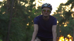Cyclist riding a bike on an open road to the sunset Stock Footage