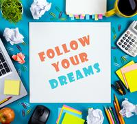 Follow your dreams. Office table desk with supplies, white blank note pad, cup - stock photo