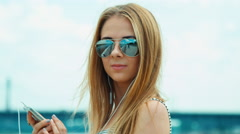 Close up portrait young adult woman in sunglasses typing sms in her cell phone Stock Footage