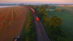 Railroad train rolling through foggy, scenic rural landscape. Stock Footage