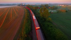 Railroad train rolling through foggy, scenic rural landscape Stock Footage