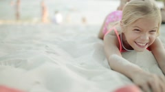 Little beautiful smiling girl lying on warm sand Stock Footage