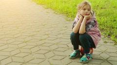 Little sad girl is sitting on basketball ball Stock Footage