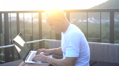 Outdoors portrait of handsome young man in sunglasses working on a laptop com - stock footage