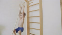 The child is engaged in gymnastics at the sports rings Stock Footage