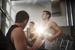 Men exercising on treadmill in gym Stock Photos