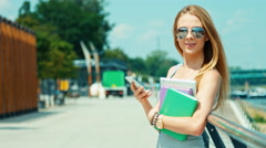 Close up portrait young woman 20-25 years using her smartphone holds textbook - stock footage